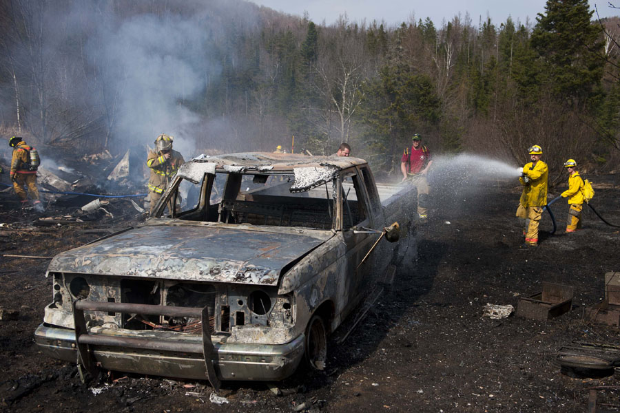 Photo by Adam Caira Barre Town Firefighers Sanborn and Stewart survey the scene of a brush fire that destroyed a 1988 Ford F-250 pickup truck and a shed containing some power equipent and other assorted tools before firefighters were able to get the blaze under control. The fire, which started at about 3:15pm, burned about an acre of Alice Smith's land on Smith Road in Orange, Vermont on Saturday, April 27, 2013. Sylvia O'Brien, Smith's daughter, was burning some old growth out of a raised garden when a gust of wind caused the fire to spread. O'Brian and another neighbor both called 911. Crews responded from Barre Town, Plainfield, and Washington, they were able to get the fire contained before it spread to Alice Smith's mobile home where she lives adjacent to the property that was scorched.