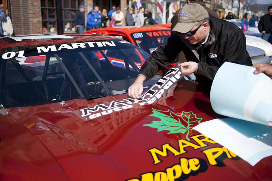 Paul Mascitti of Mascitti Bros. Custom Vinyl Lettering applies a last-minute decal to the Martin Maple Products race car from Craftsbury Vt. at the start of the Thunder Road Car Show on Main Street in Barre, Vermont on Saturday, April 27, 2013.