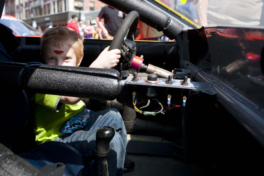 John (Jac) Cattier Jr., 5, sits in the driver seat of the Froggy 100.9 #46 race car at the Thunder Road Car Show on Main Street in Barre, Vermont on Saturday, April 27, 2013.