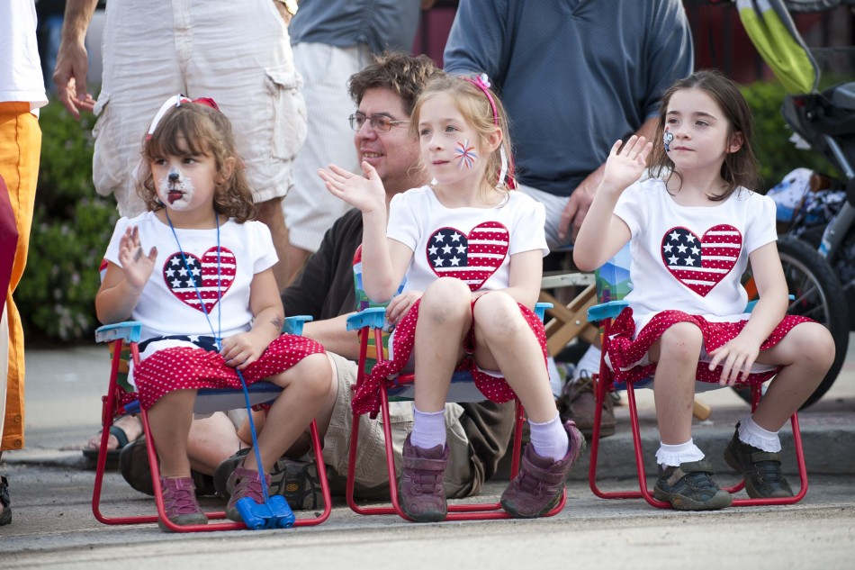 Photo by Adam Caira Children watch the parade pass on State Street in Montpelier Vt., on Wednesday, July 3, 2013., part of Montpelier's Independence Day Celebration.