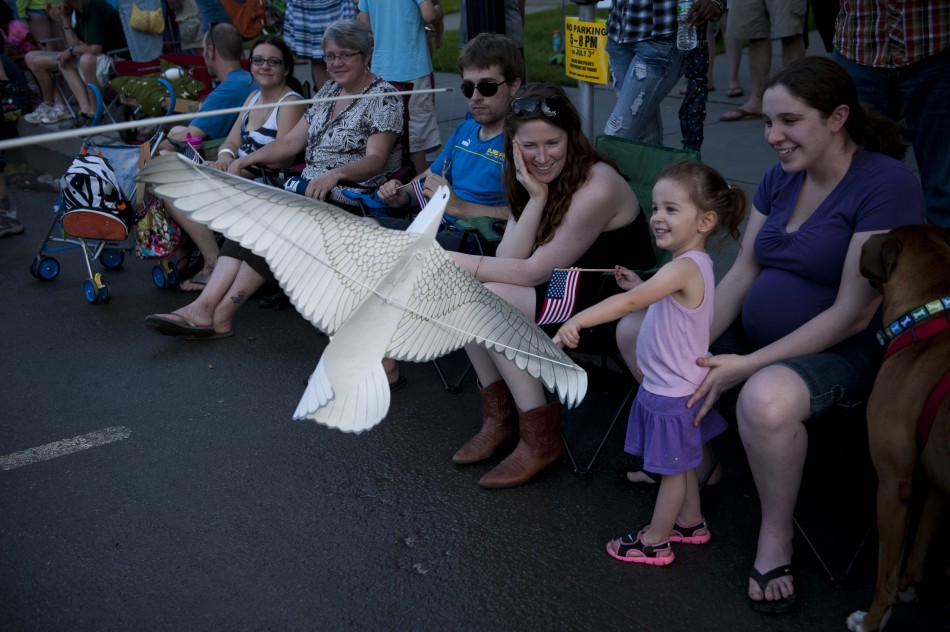 Photo by Adam Caira Emily Badger, 2, interacts with a paper dove with her mother Megan Badger, far right, while watching the parade on State St. in Montpelier Vt., on Wednesday, July 3, 2013., part of Montpelier's Independence Day Celebration.