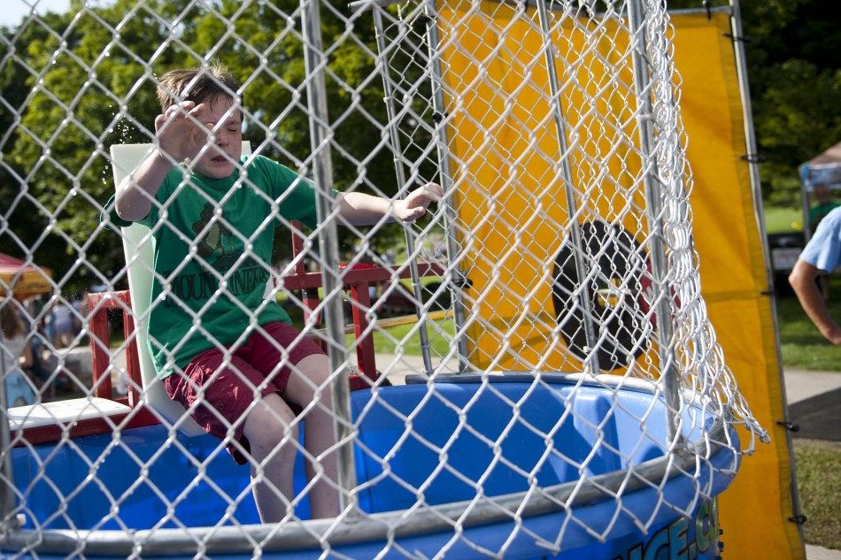 Photo by Adam Caira Zane Odum, 9, is dunked by his brother, Tucker Odum, 13 in a dunking both on State Street in Montpelier Vt., to raise money for the U-32 boys and girls hockey teams to travel to Munich, Prague, and the Czech Republic in April 2014 to participate in a tournament, on Wednesday, July 3, 2013., part of Montpelier's Independence Day Celebration.