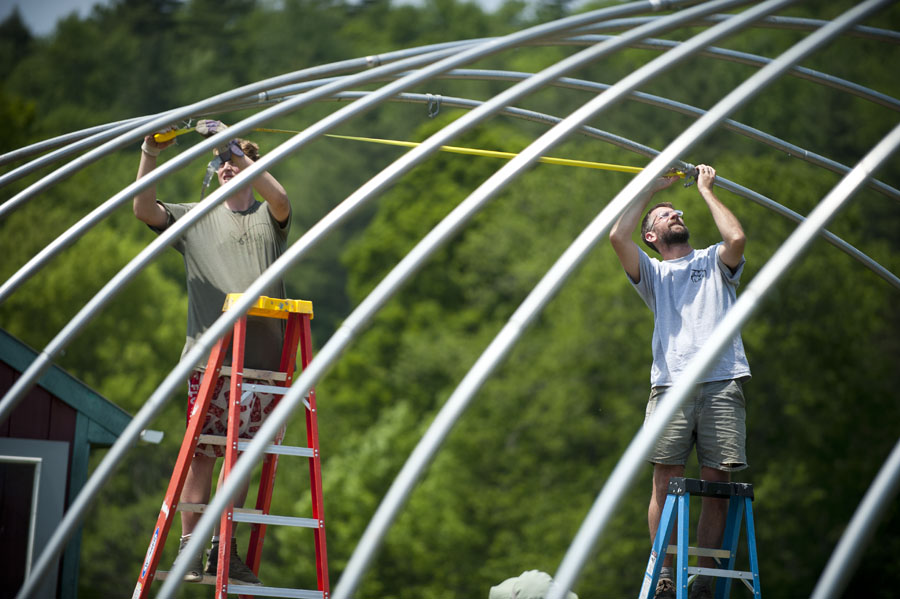 Photo by Adam Caira l-r Jon Kilian, a sophomore at Montpelier High School and Matt Mclane, Coordinator of Community Based Learning at Montpelier High School work to find the center point on the newly erected rafters of a hoop greenhouse behind Montpelier HIgh School. The structure will be used to grow tomatoes and peppers, the ingredients for salsa.