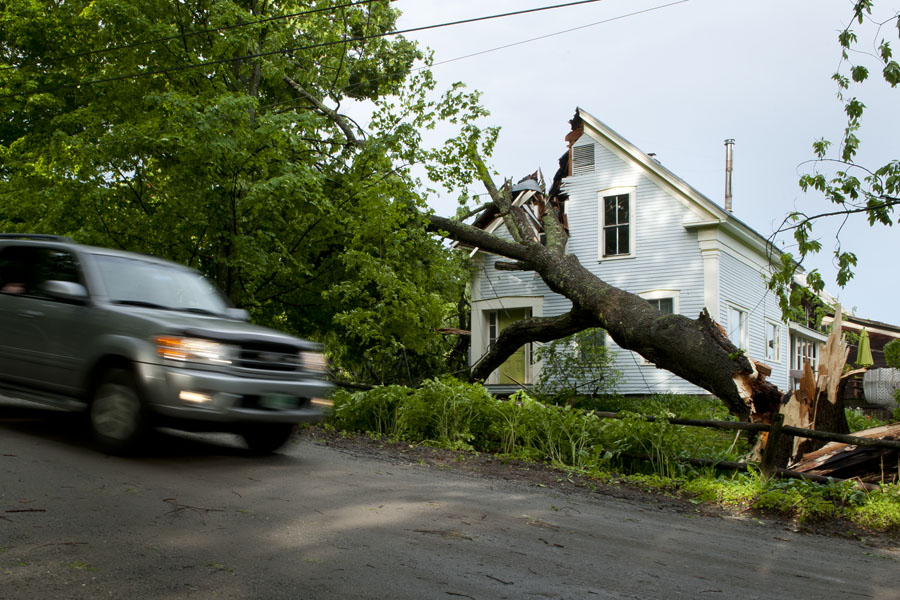 Photo by Adam Caira A car slows as it passes a home damaged by a wind-blown tree on Hollister Hill Rd in Plainfield Vt. on Sunday, June 2, 2013. According to neighbors the home is owned by Leslie Rabins who also owns One More Time in Montpelier. Neighbor David Ertel who lives two houses down on the opposite side of the road was home when the storm hit, several cedar trees fell in his yard in addition to one that fell across Hollister Hill Rd. Ertel and his neighbors were able to use a chainsaw and a tractor to remove the tree blocking the road, one of many that fell on Hollister Hill.