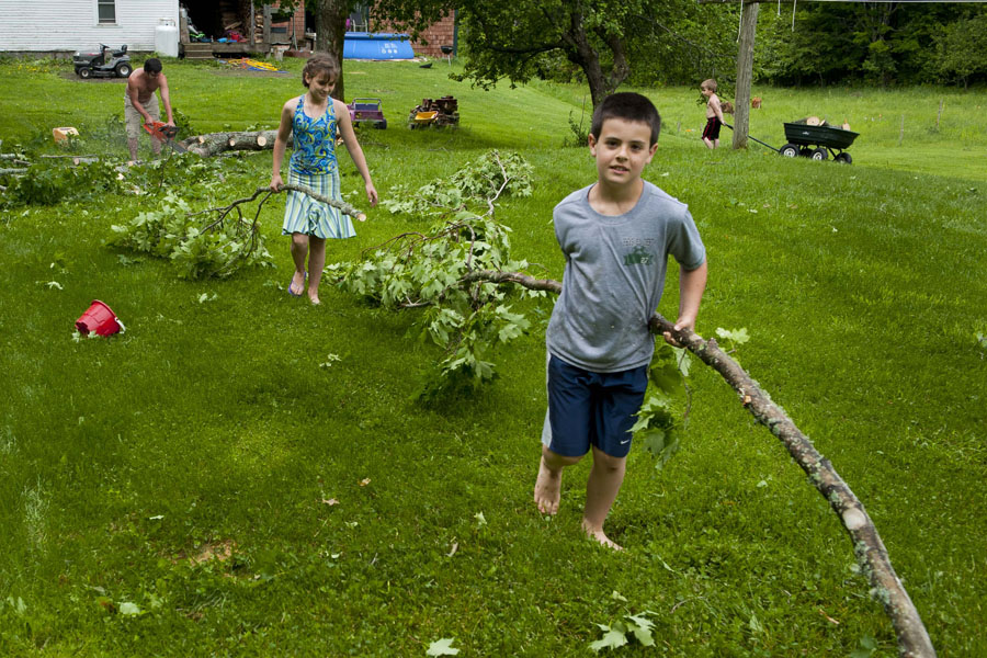 "Photo by Adam Caira L-r Dave Mulligan and his children Bride Mulligan, 10, Anthony Mulligan, 8, and Raphael Mulligan, 4, work to cut and remove fallen trees from the property where they live along with Dave's parents on Hollister Hill Rd. in Plainfield on Monday, June 3, 2013. Dave's mother Alice Mulligan, not pictured, recounts how during the storm it was raining and blowing so hard ""We couldn't see from our house to our barn."" some 60 feet away."