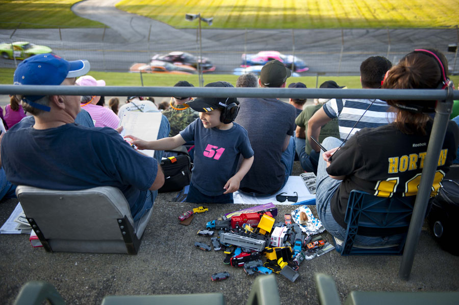 Photo by Adam Caira Kolton Williams, 5, of Georgia, Vt., plays with a toy car with his Grandfather Dick Bradley, at left, of Randolph, and his mother, Sarah Williams, at right, of Georgia, Vt., during the Late Model semi-feature at Thunder Road in Barre, Vt. on Thursday, June 20, 2013.