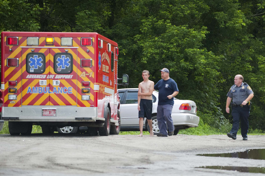 Photo by Adam Ciara The first of two victims walks to an ambulance on Parkside Terrace in Barre. Rescue crews removed two men from the Jail Branch just below Spaulding falls in Barre Vt. on Tuesday, July 2, 2013. Crews accessed the scene by cutting a path from Parkside Terrace near the Barre City Pool.
