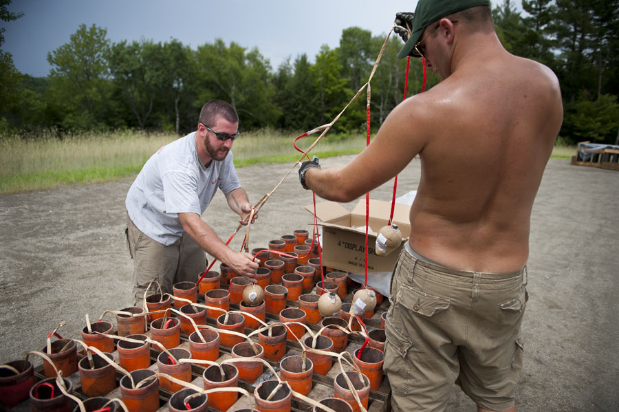Photo by Adam Caira l-r Lead Shooter Alex Kaigle and Axel Larson drop a string of fireworks into their launch tubes while preparing the finale for the Montpelier Independence Day fireworks show put on by Northstar Fireworks