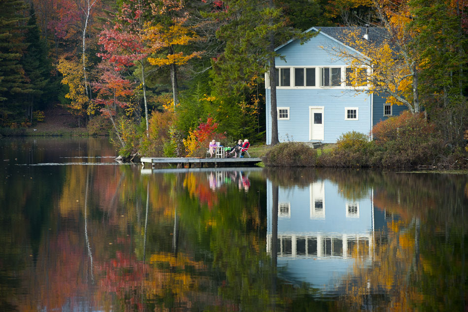 A group of people sit on the dock of a home surrounded by fall foliage on Curtis Pond in Cabot Vermont on Friday, Oct. 8, 2012.