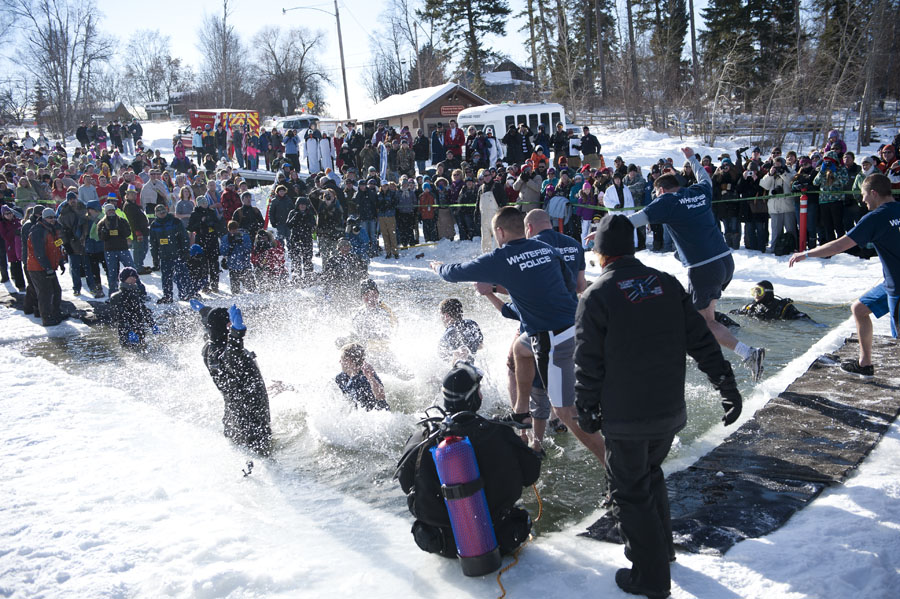 Whitefish Police Officers and their families take the plunge in the frigid water of Whitefish Lake during the Winter Carnival Penguin Plunge Feb. 8, 2014